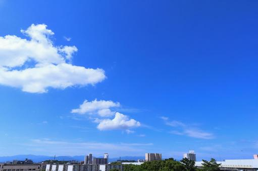 Autumn sky with beautiful white clouds floating in the bright blue sky