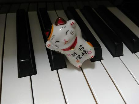 Piano keyboard and beckoning cat