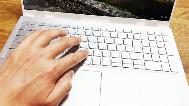 Left hand operating a laptop