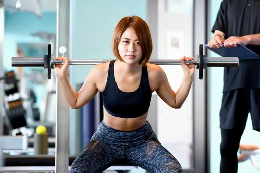 Young woman squatting in the gym