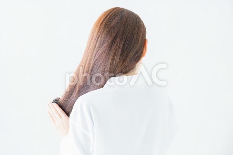 髪をくしでとかす女性の写真
