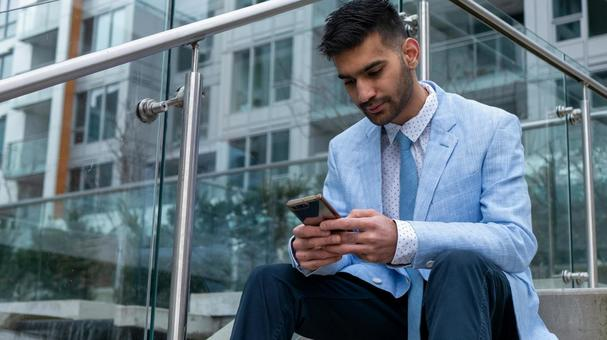 휴대 전화를 계단에 앉아 만지는 사업가