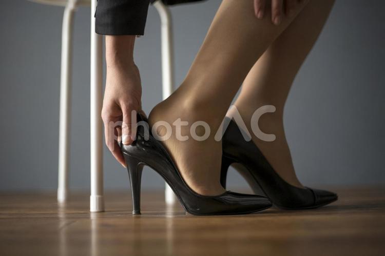 足に痛みを抱えるビジネス女性の写真