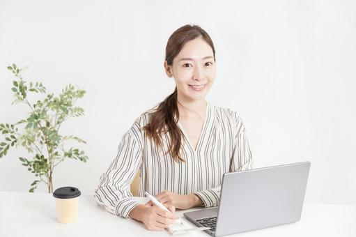 Woman taking notes with work