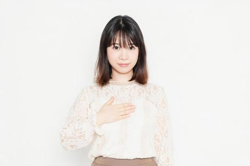 A young woman in a lace blouse standing in front of a white background and putting her hands on her chest