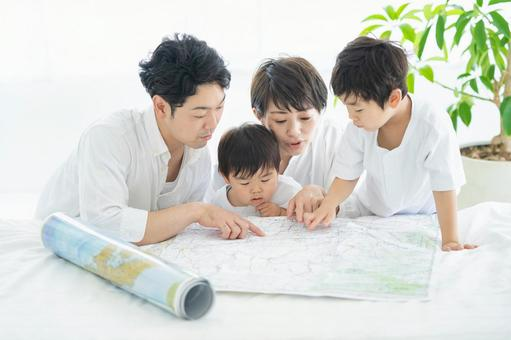 Parents and children studying happily using maps ・ Parents and children planning trips using maps