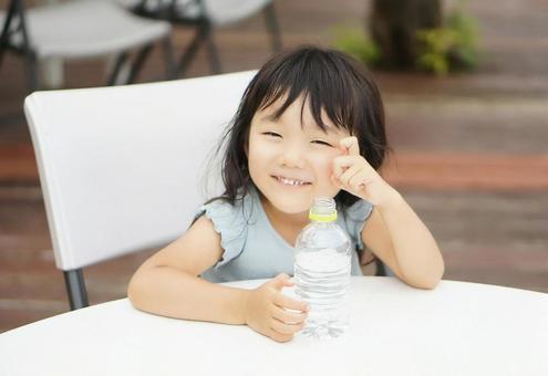塑料瓶裡的水和一個微笑的女孩
