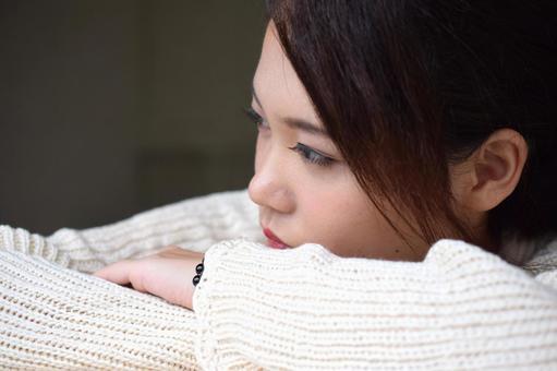 슬픈 눈빛으로 무언가를 응시하는 여성