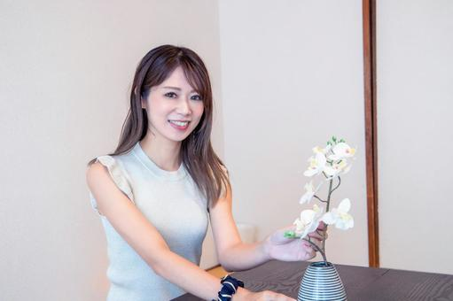 A woman with flowers and a smile in a Japanese-style room
