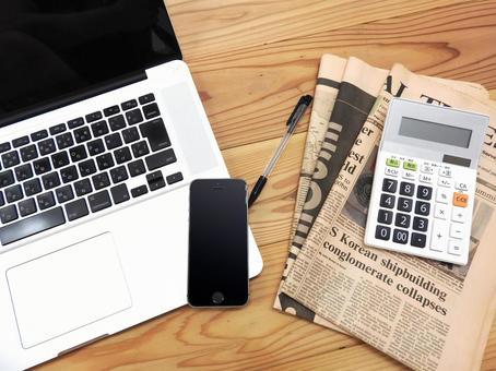 pc, smartphone, pen, calculator and English newspaper