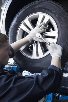 Automobile mechanic servicing tires 12