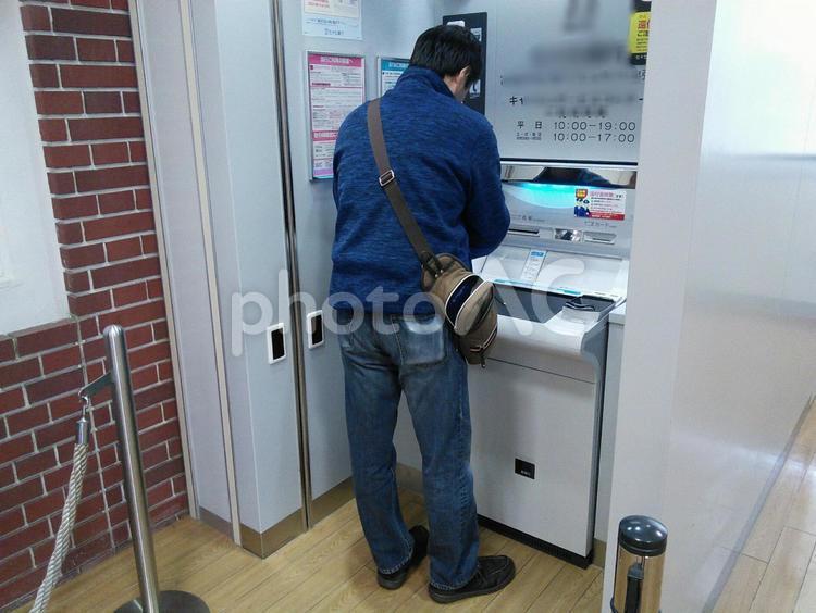 Atmでお金をおろす 日本人の 50代の男性の写真