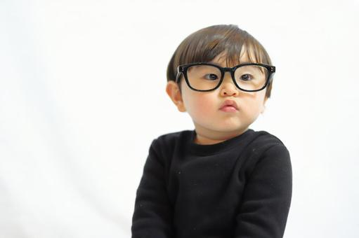 A child wearing glasses and looking straight ahead