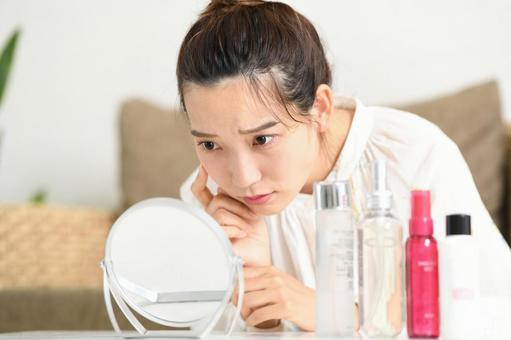 A woman suffering from skin problems while looking in the mirror