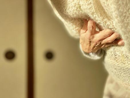 Elderly hands holding the chest