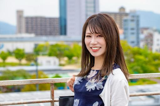 A smiling woman against the backdrop of the city of Hiroshima