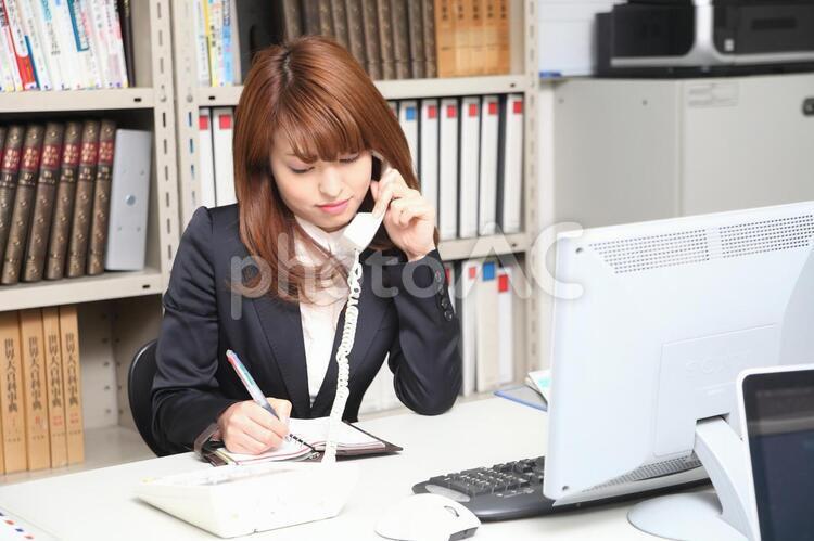 電話しながらメモを取る女性2の写真
