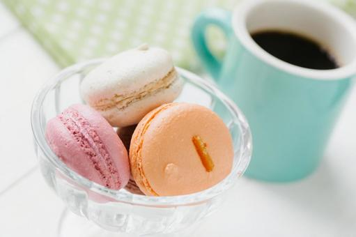 Macaroons and coffee placed on a white wood board