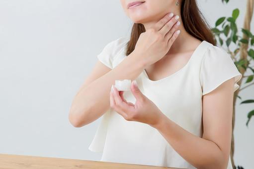 Woman applying cream on the neck