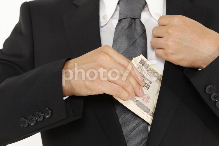 現金をポケットに入れる男性5の写真