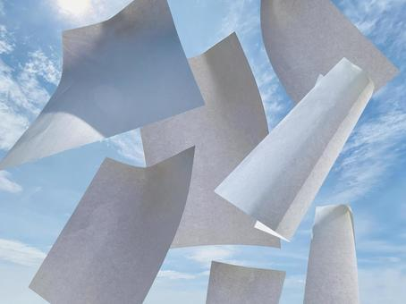 Blank paper scattered in the blue sky