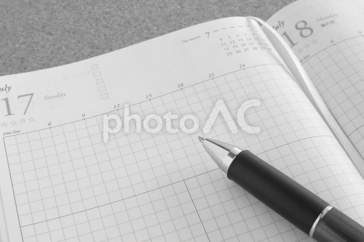 スケジュール帳とペン モノクロの写真