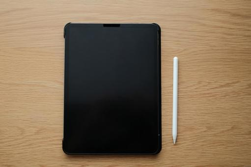 Overlooking the tablet terminal and touch pen on the wooden desk
