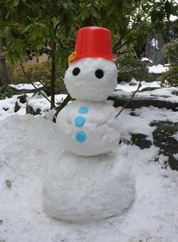 A snowman wearing a red bucket