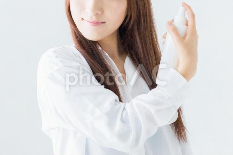ヘアスプレーする女性の写真