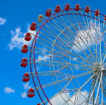 Red Ferris wheel in the clear blue sky of summer