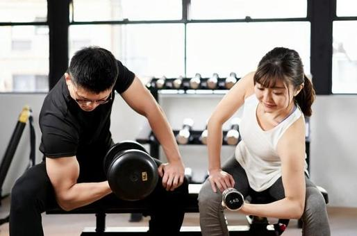 Asian men and women with dumbbells in the training gym
