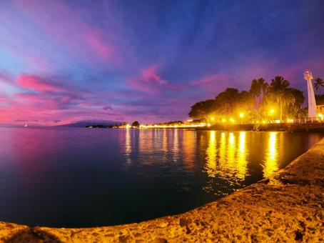 Sunset sea and city lights