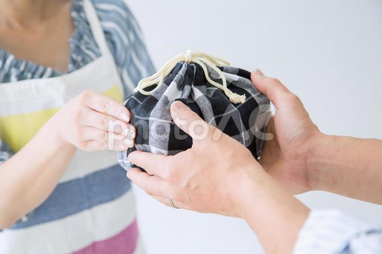 男性にお弁当を渡す女性の写真