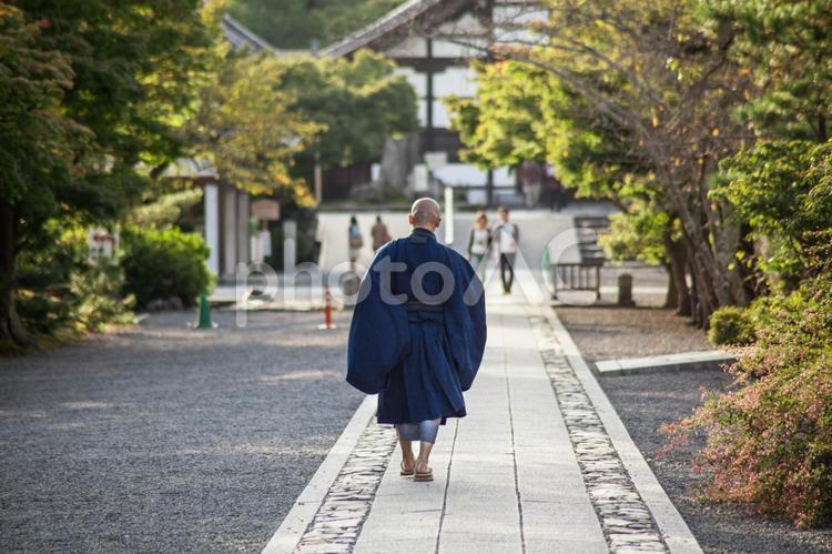 石畳を歩くお坊さんの写真