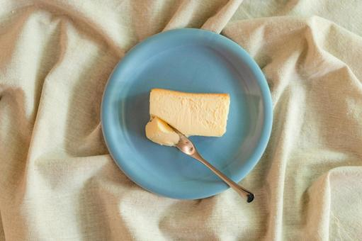Light blue plate and baked cheesecake placed on a linen tablecloth