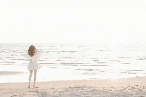 해변을 걷는 흰 원피스 여성