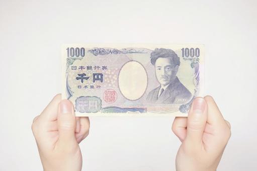 Both hands holding a 1000 yen bill