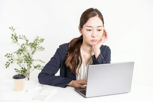 A woman who operates a computer while being quietly angry