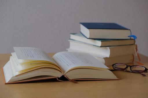 見開きの本と積まれた本と眼鏡