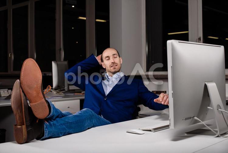 PCの画面の前で机に足を上げたままため息をつく男性の写真