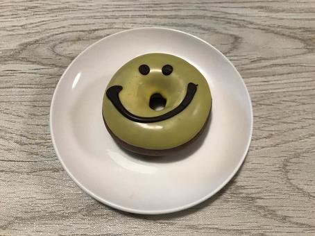 Smiley donuts on a small white plate placed on a wooden table