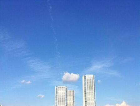 An airplane cloud across the blue sky