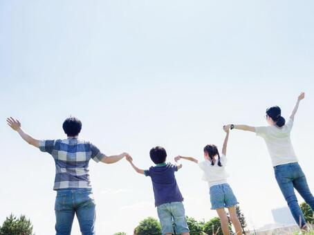Family holding hands in a sunny park