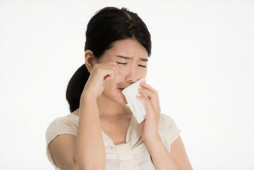 A woman suffering from a medical condition while blowing her nose with tissue