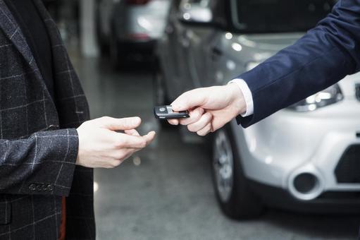 A dealer of a car dealer who hands the key 1