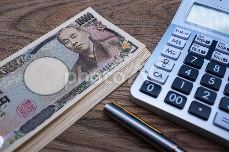 お金と電卓イメージ背景の写真