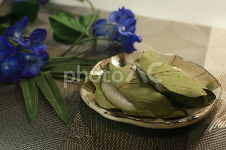 お皿にのった柏餅と笹と花の写真
