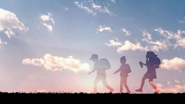 Three children walking with school bags on their backs_sunset and cloud background