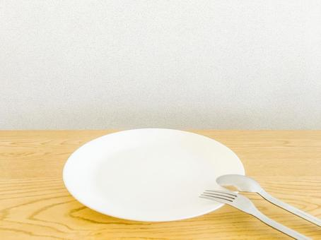 White plate, table and white wall Dining table image