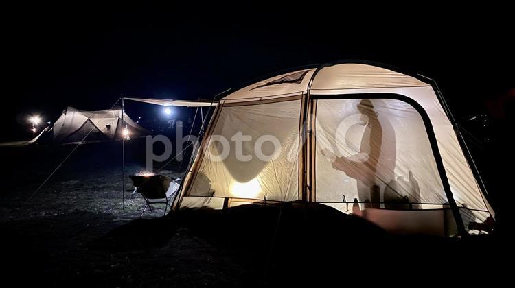 夜のテント内で本を読む女性のシルエットの写真